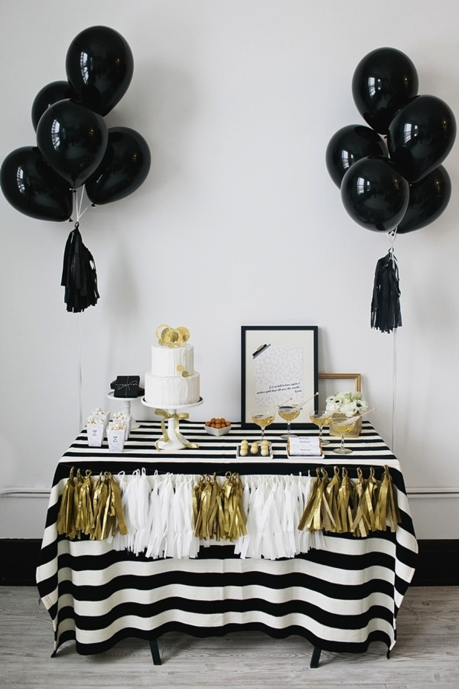 { Via } Gold, gold, and more gold! Create a dessert table with a black table cloth covered in gold streamers with black balloons, festive cake, snacks, and more