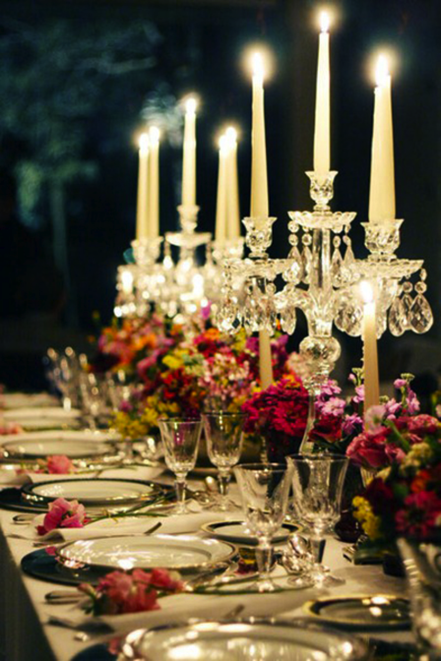 These jewel tone blooms look wonderful mixed with the simple table setting and candelabras { Via }
