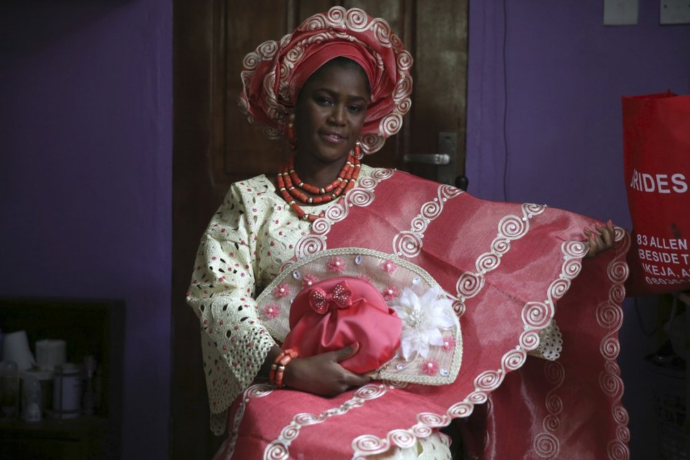 This beautiful Nigerian bride is traditionally dressed in a brightly colored lace blouse and patterned kaftan. She has on coral beads and a headdress to bring the wedding attire together. The bride can decide on what color she would like her blouse and kaftan to be and matches her beads and headdress accordingly.