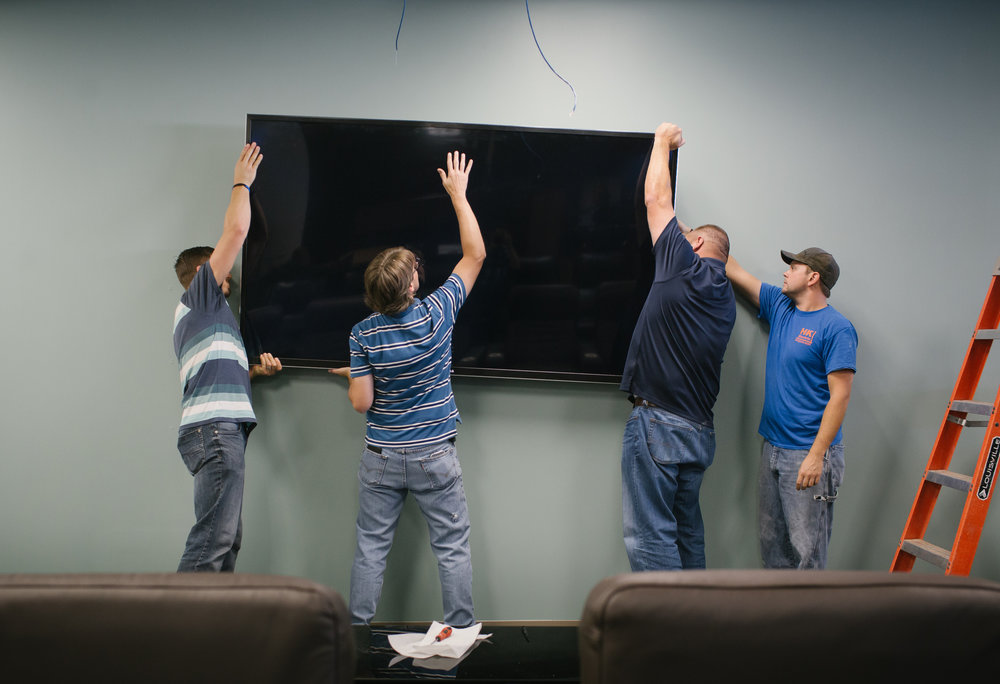 PILR TECH employees, from left to right, Ryan Meredith, Michael Black and Michael Cory and Matthew Williams, with HK Electric, install an 85 inch tv at their office in Joplin, Mo. Photo by Brad Zweerink