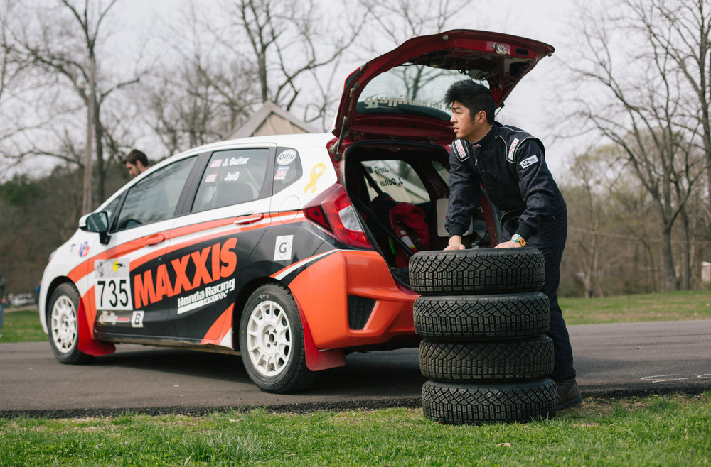 Co-driver William Jang pulls tires out of his 2015 Honda Fit rally car.