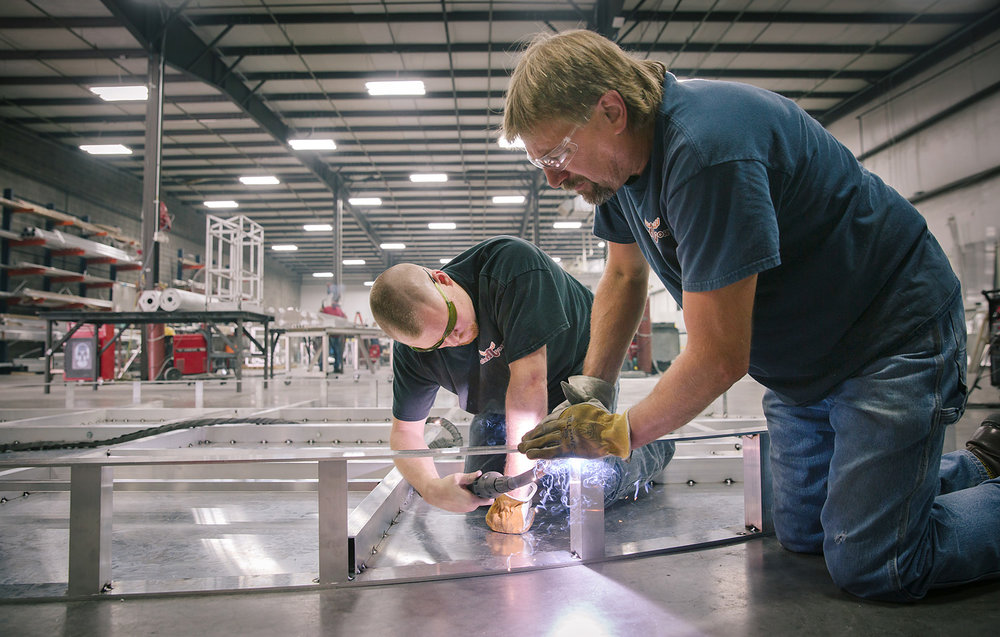 Nick Nimmo, left, and Patrick Brewer weld the frame of a metal sign at Elemoose's facility in Springfield, Mo. on July 18, 2017. Photo by Brad Zweerink.