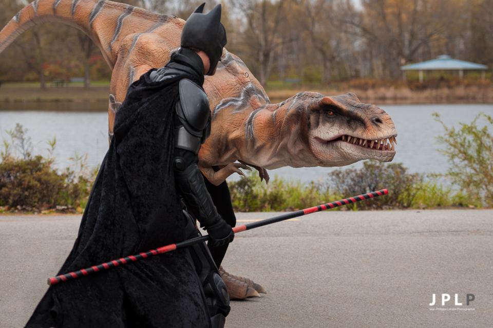 Batman contenant calmement un bébé tyranosaure.