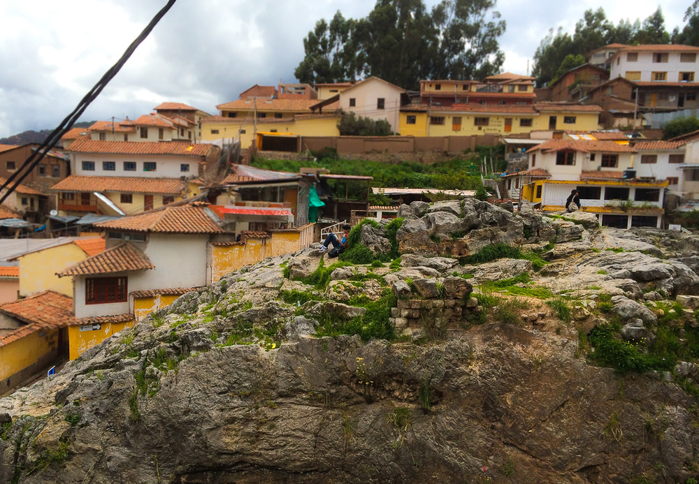 A boy reads on a hilltop in Cusco, Peru