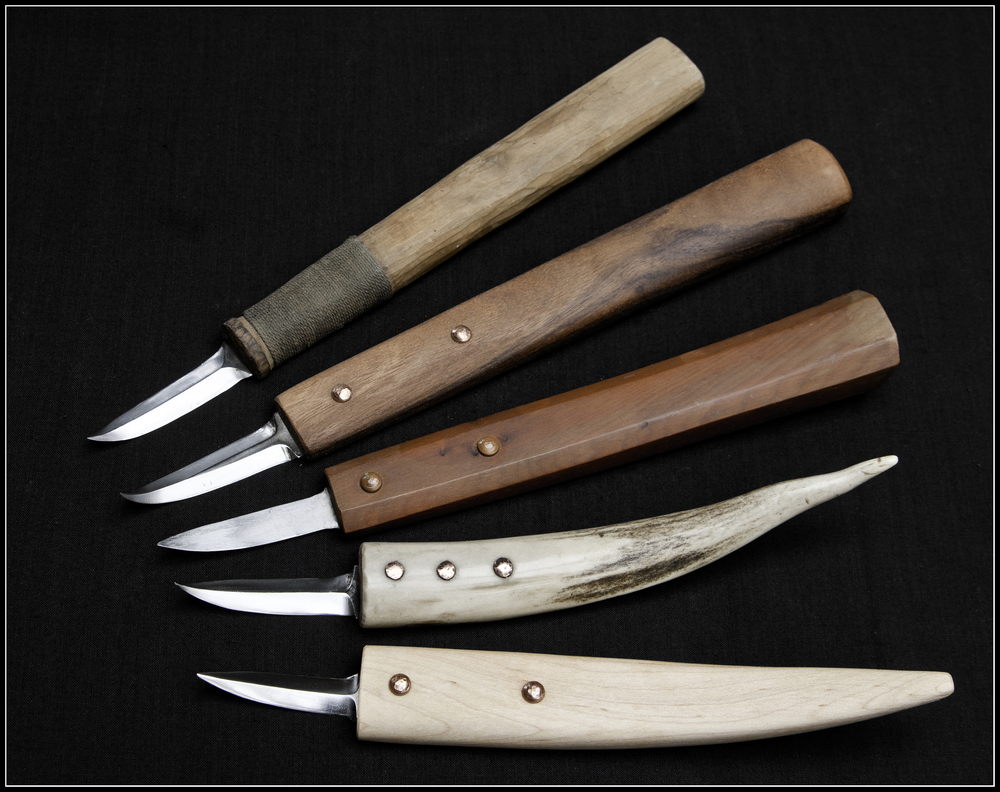 Various incarnations of the Kestrel crooked knife through the years.