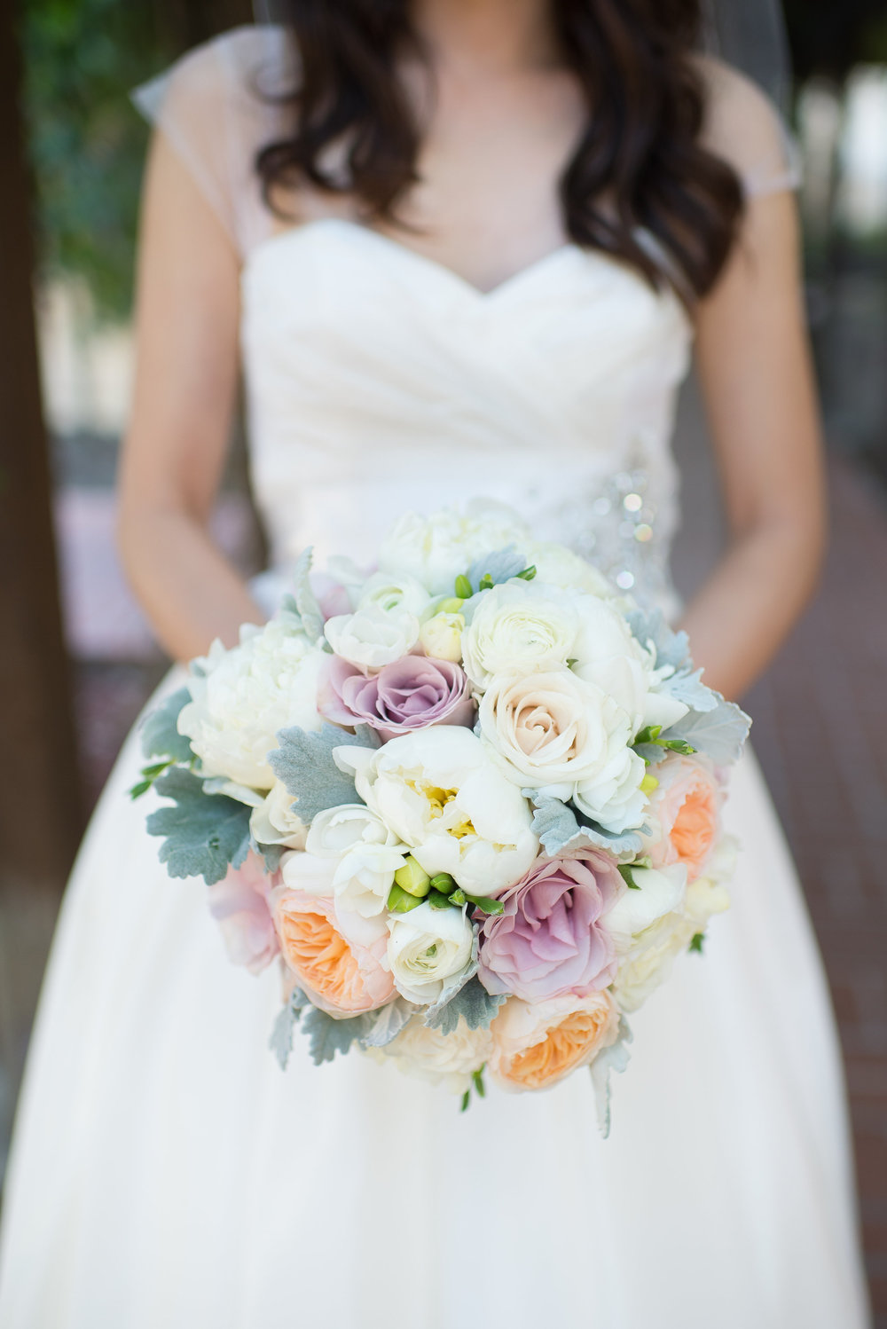"Peachers carried a bouquet of peach, blush and ivory flowers: white peonies, peach garden rose "" juliet"" , white freesia, and white ranunculus with dusty miller."