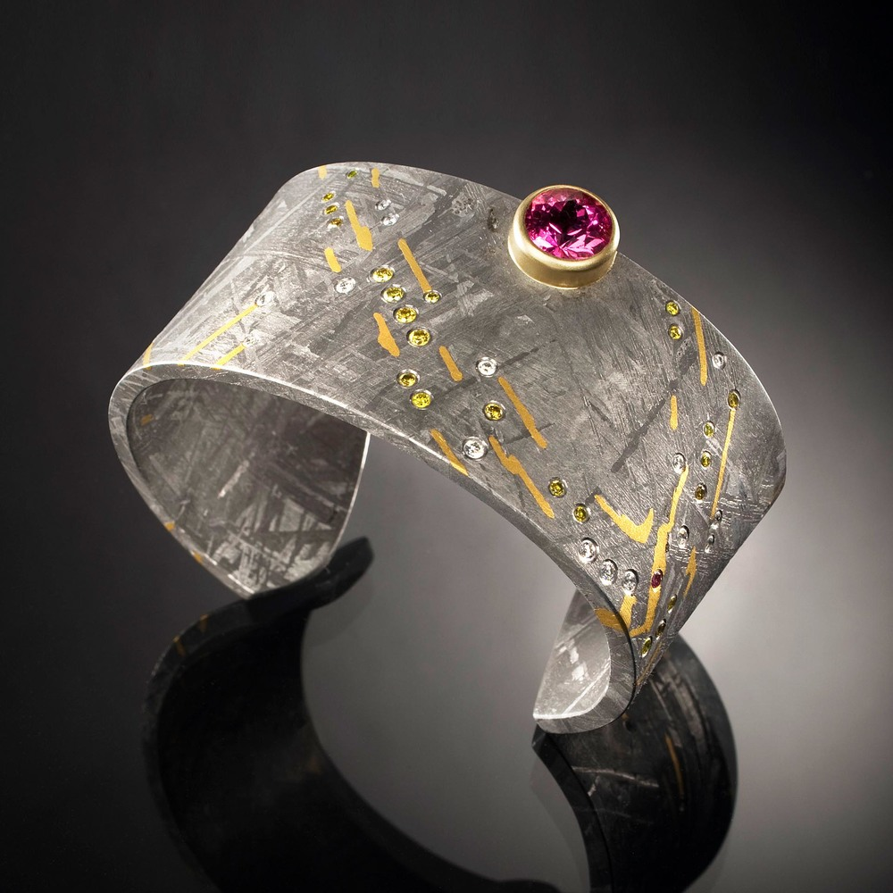 Meteorite cuff bracelet with 24 karat gold inlay, with white and yellow diamonds, rubies and one off-set rubellite tourmaline.
