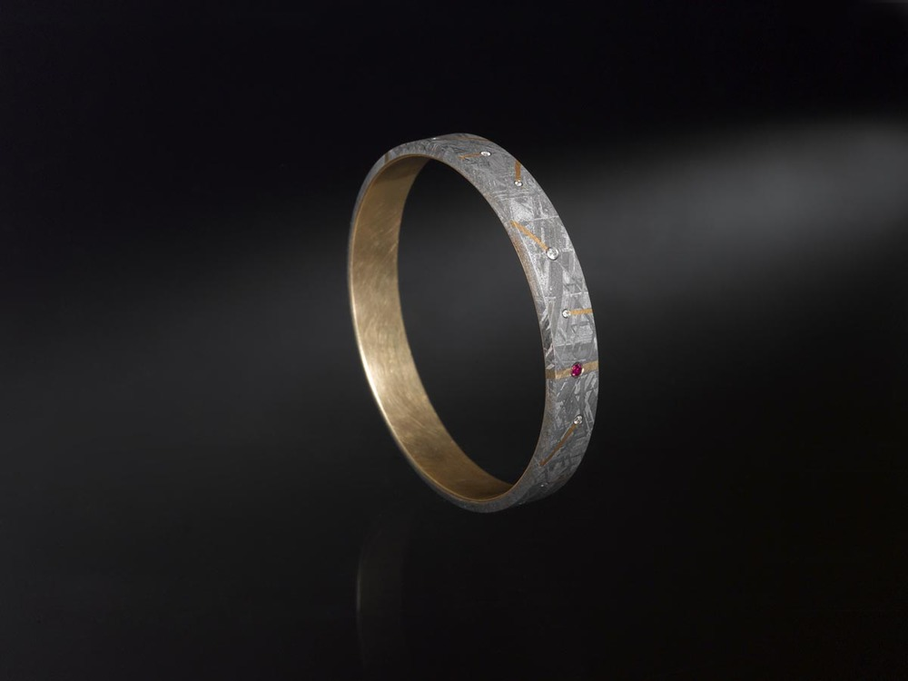 This bangle is lined with 18 karat yellow gold. It has 24 karat gold inlay, one ruby and several diamonds set into the meteorite.