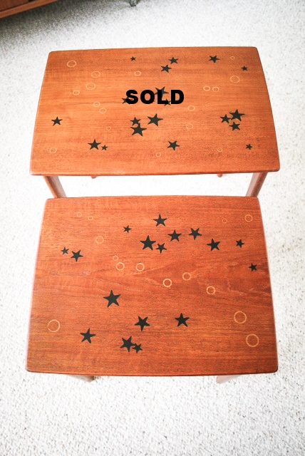Stacking teak tables with inlays of circles and stars.