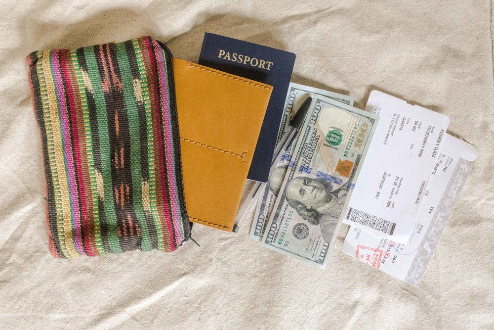 Pictured is my personal travel pouch and everything I keep inside. Passport (with cover), cash, pen, and boarding passes.