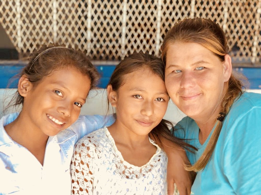 Connect Global Team Member sharing a hug with two girls from El Tamarindo