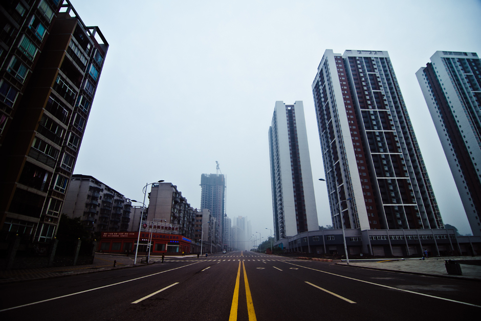 Chongqing ,  China . Newly constructed high-rise apartments dwarf the empty street below. Chongqing is one of China's most densely populated regions with nearly 1000 people per square mile.