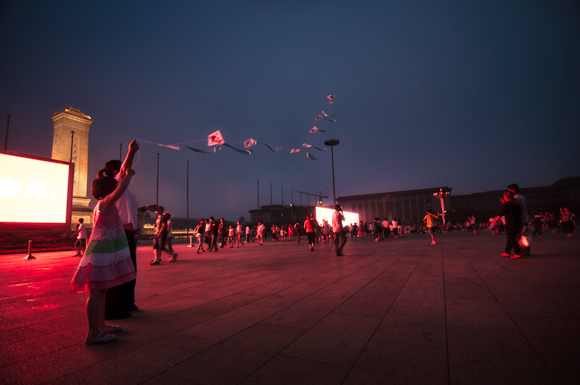 A girl and her mother fly a kite in Tiananmen Square, Beijing, China. July, 2011.