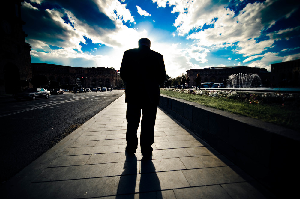 An elderly man shuffles through Republic Square where Lenin's statue once stood