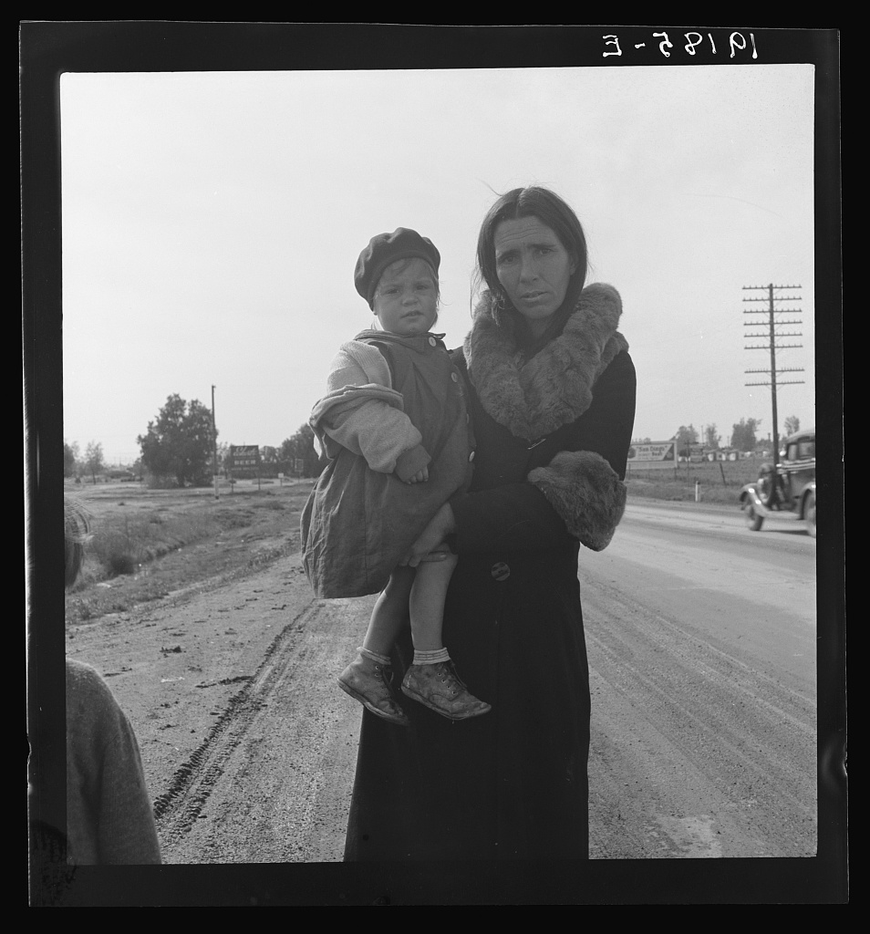 "On U.S. 99. Near Brawley, Imperial County. Homeless mother and youngest child of seven walking the highway from Phoenix, Arizona where they picked cotton. Bound for San Diego, where the father hopes to get on relief ""because he once lived there."""