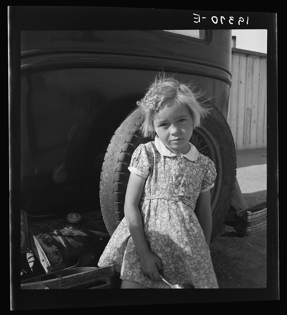 Arkansas girl in migrant camp near Greenfield, Salinas Valley, California. This is an Arkansawyers auto camp, filled almost completely with Arkansawyers recently in California. Rent ten dollars per month for one room, iron bed, electric light. (This community is subject of a study by Regional Office, BAE, Land Utilization Division, Berkely, California)