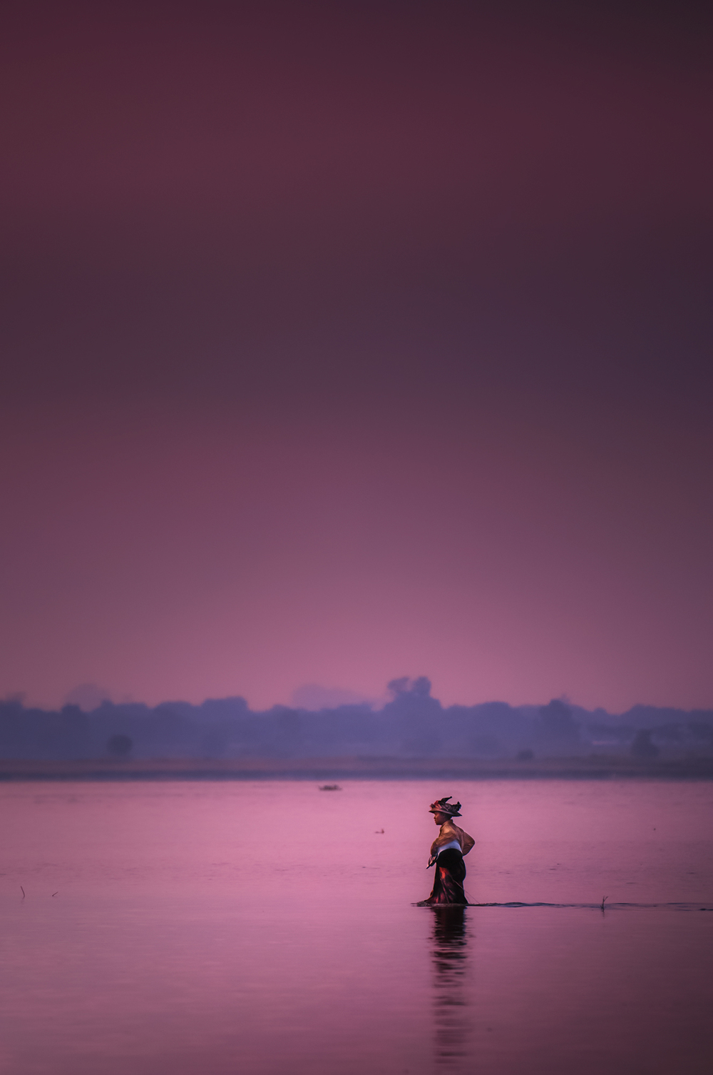 A woman wades  through the water beneath U Bein's bridge toward more fertile fishing grounds.