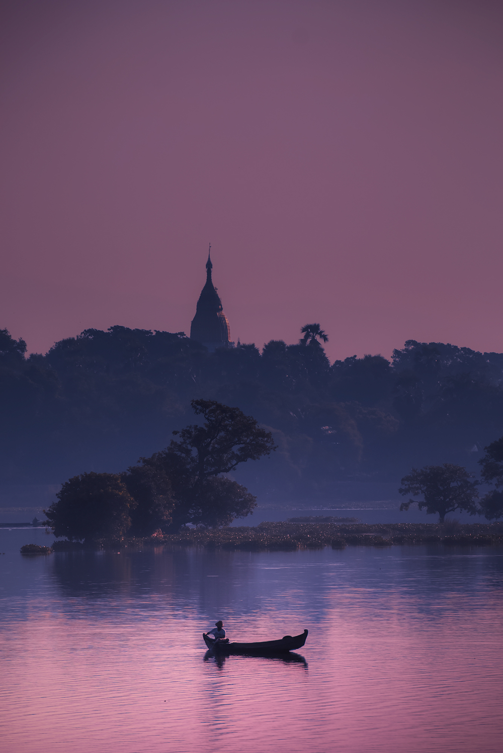 A fisherman  navigates Taungthaman Lake in the shadow of a distant stupa at dawn.