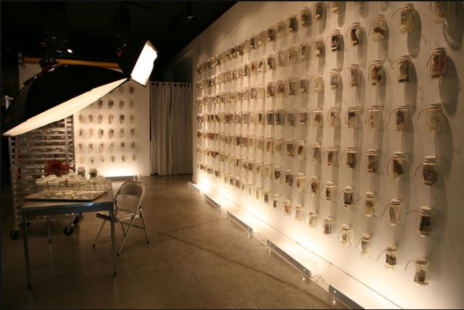 What's on Your Mind Installation, Approximately 300 bottles sealed with wax with imagery insided embedded in wax and FB posts on labels on bottles.