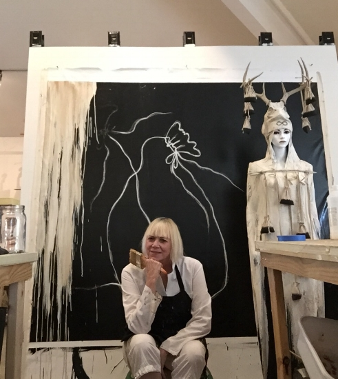 "Judith Kindler sits in front of ""Protector"" painting and assemblage sculpture in her studio preparing to go to the Seattle Art Fair and part of her newest body of work ""Of What Importance"""