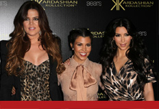 Kourtney and Kim step on some apple boxes to take a photo with their sister.
