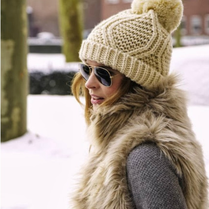 A knit pom pom beanie is both youthful and stylish; paired with classic aviators and a fur waistcoat is perfection.