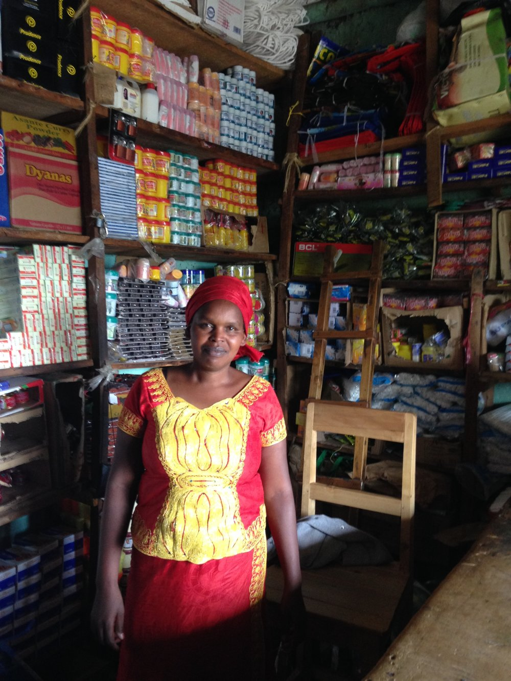 A microentrepreneur in Rwanda stands in front of her store.