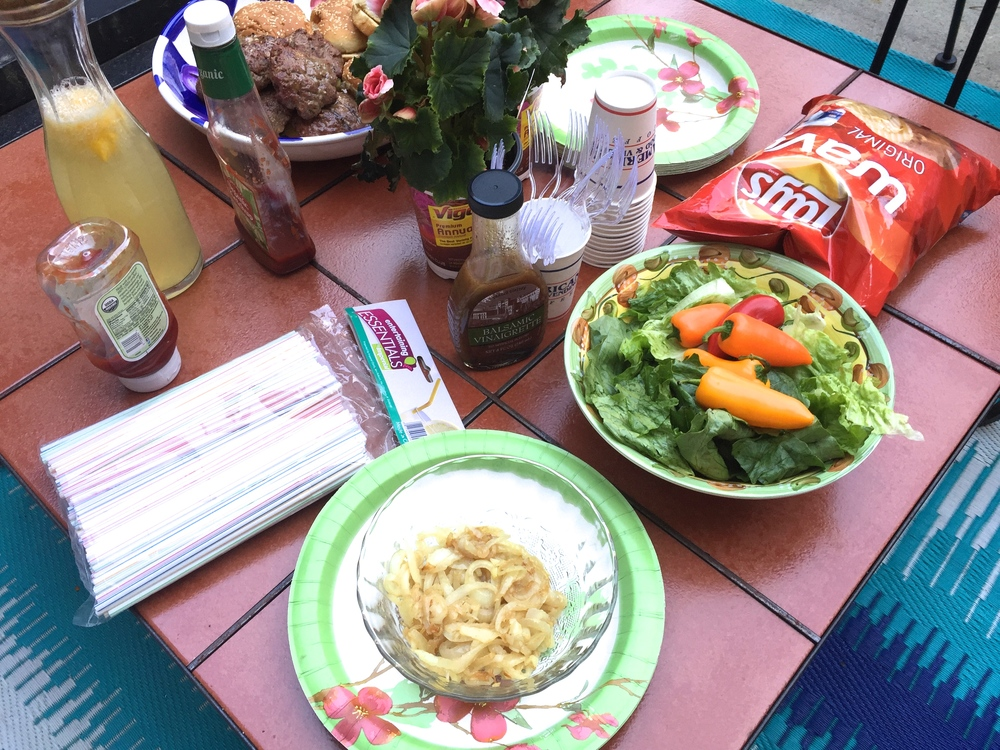 Just add something raw...greens and sweet peppers for today, some extras for fun...chips, and carmelized onions to top off that burger. Flowers and printed paper plates make for the perfect casual outdoor dinner setting.  Bon Appetit!