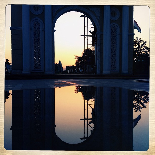 The sun sets over the national flag and arches in the center of town in the main park of Dushanbe, Tajikistan. (at Dushanbe, Tajikistan)