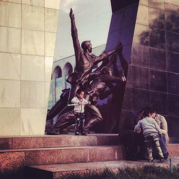 A family sits by a memorial commemorating the 2010 Revolution that overthrew Kurmanbek Bakiyev. This revolution was preceded by the Tulip Revolution in 2005, during which Askar Akayev was forced from power. (at Bishkek, Kyrgyzstan)