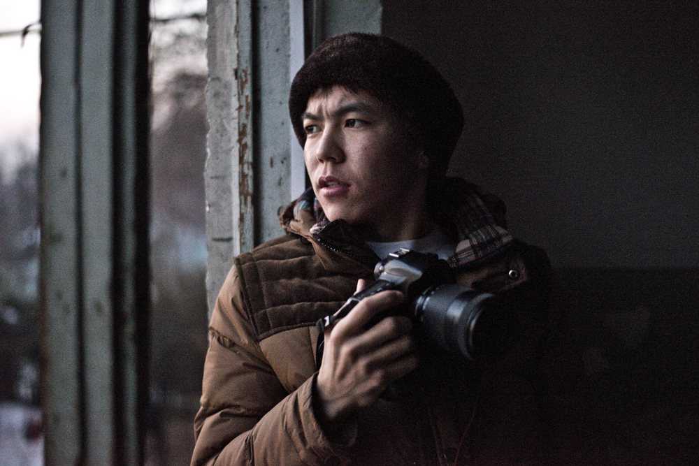 Photographer and journalist Dastan Umottegin looking out from his apartment building in Osh, Kyrgyzstan.