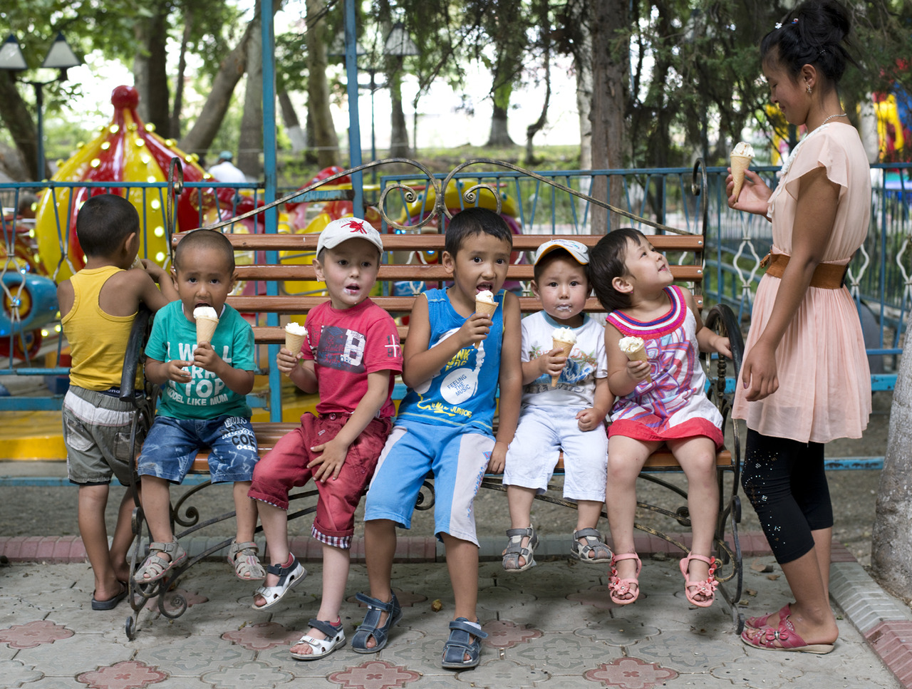 A babysitter watches over a group of kids as they eat ice cream in one of the several permanent parks established during the Soviet Era in Osh, Kyrgyzstan. The permanent amusement park is about 800m long and features bumper cars, cotton candy, bb guns, numerous outdoor venues for restaurants, and karaoke booths among other shops. The park offers an economic opportunity for at least 100 families to make a living maintaining an attraction, as well as provides a source of entertainment for the rest of the public.