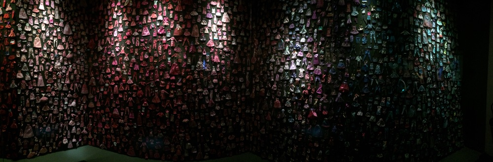 A wall of Barbie clothes organised by colour!