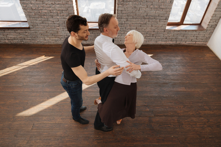 Proficient dancer teaching retired couple in the ballroom