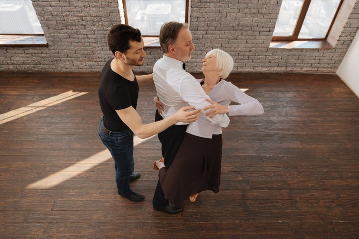 Proficient dancer teaching retired couple in the ballroom