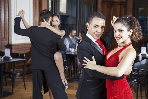 Confident man dancing the tango with a woman. Dance lessons with men meeting women and exercising