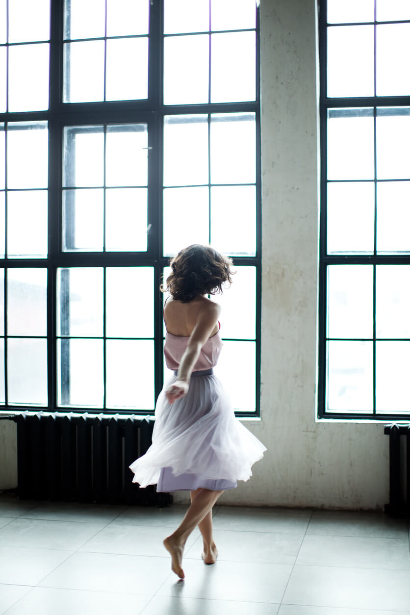 Twirl. Woman in a dress doing a spin in a dance studio