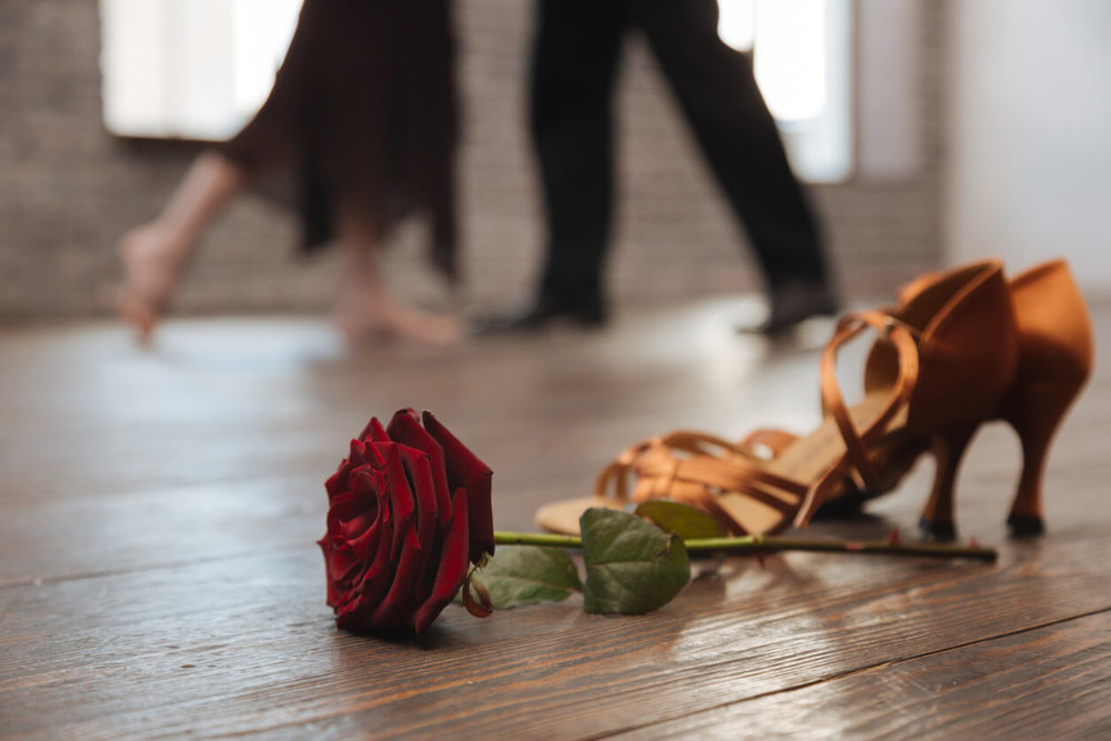 Couple shares a romantic dance in a dance studio. Taking dance lessons for Valentine's Day with rose and heels in foreground