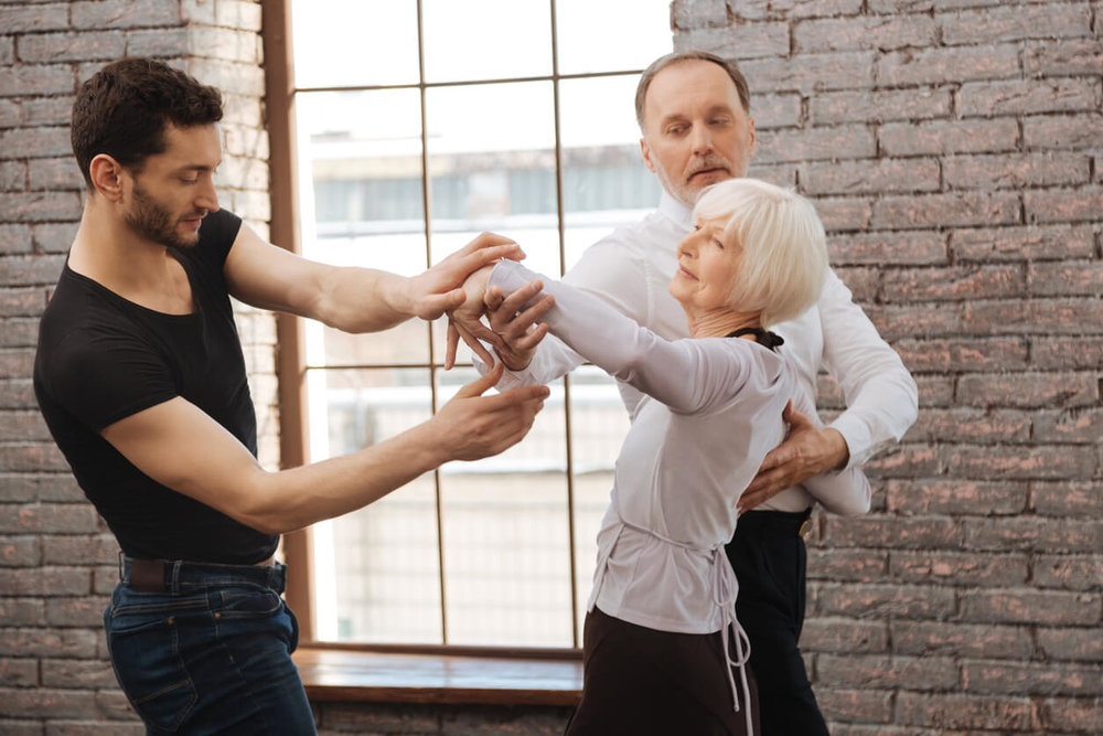 Ballroom Instructor - talented dance instructor teaching senior couple ballroom dancing lessons