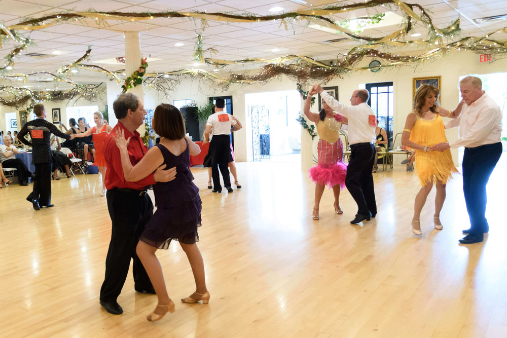 Couples dancing rumba at a studio dance competition