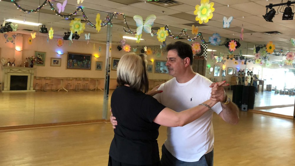 Wedding dance lessons. Couple practicing dance moves for their wedding.