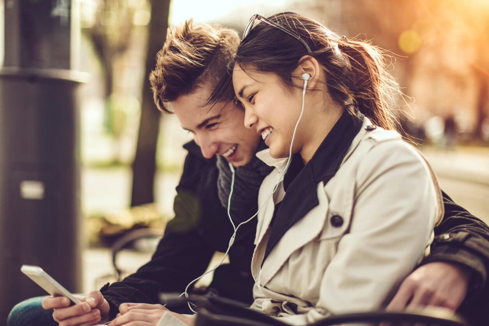 Choosing Your Perfect Wedding Song - Young couple is listening music on their mobile phone choosing their perfect wedding song