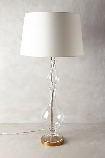 A Glass base allows for height, yet does not take away from the space. Hourglass Lamp by Anthropologie