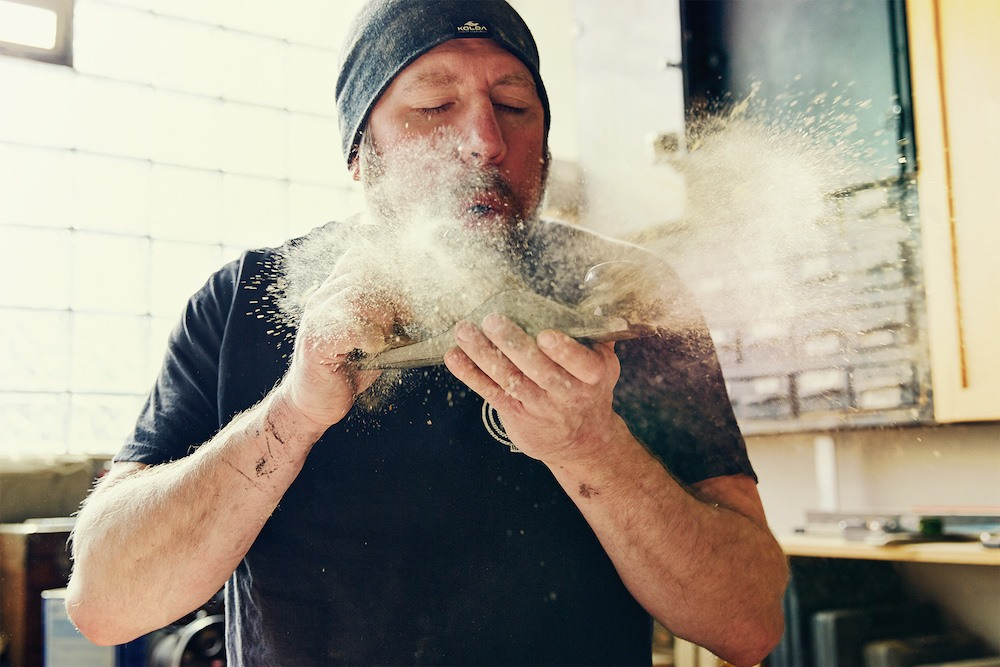 Woodshop-worker-blowing-dust-off.jpg