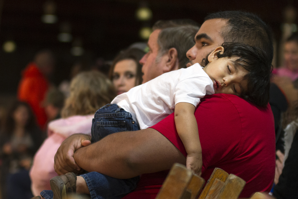 Adrian De Leon Jr., 16 months, sleeps on his father's shoulder during intermission.