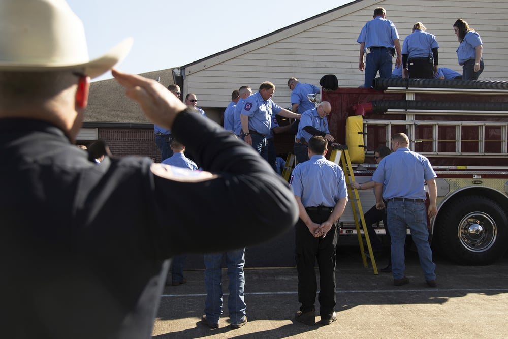 Henry's casket is loaded onto a firetruck outside the Oaklawn Funeral Home Chapel in Edna, TX.