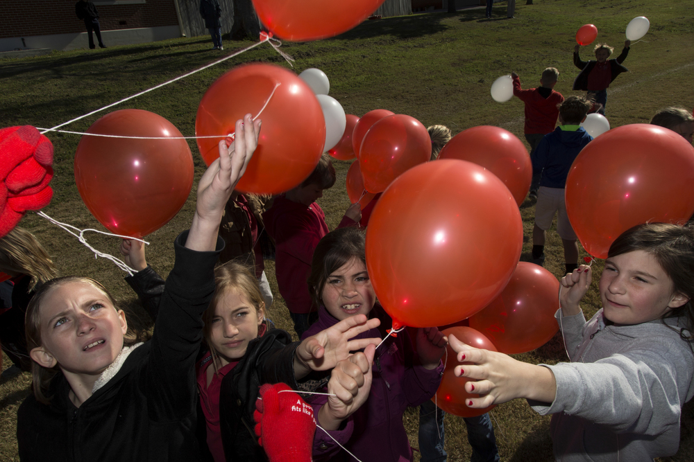 Students of Shiner Catholic School grab balloons as part of Catholic Week's balloon launch on Wednesday, February 3, 2016, in Shiner, TX. Following a countdown from the local radio station, over 600 balloons were released into the sky.