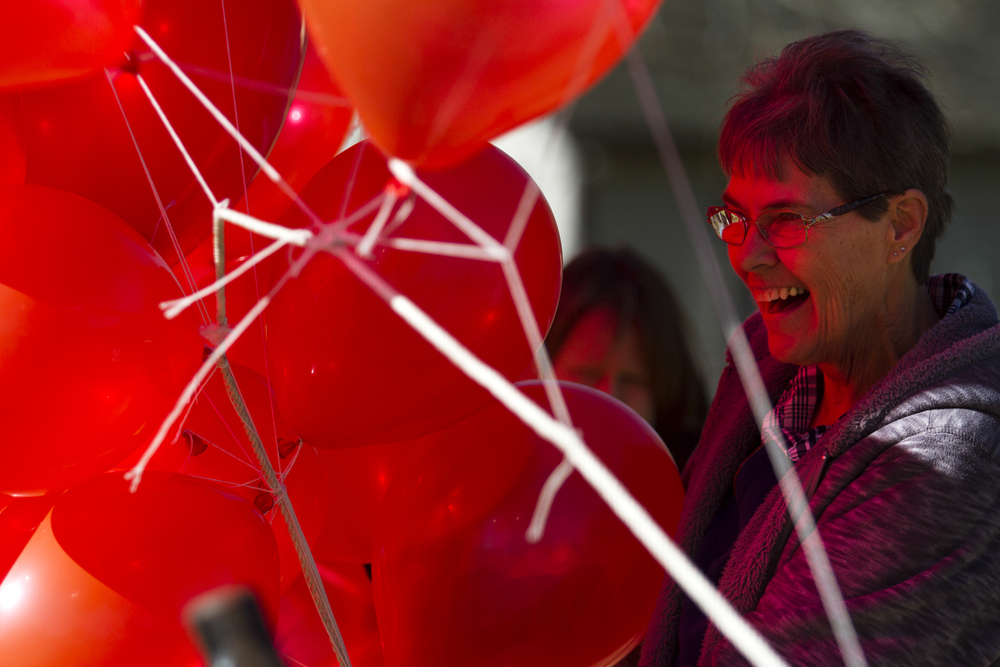 Volunteer Barbara Klozik helps tie down balloons outside near the football field.