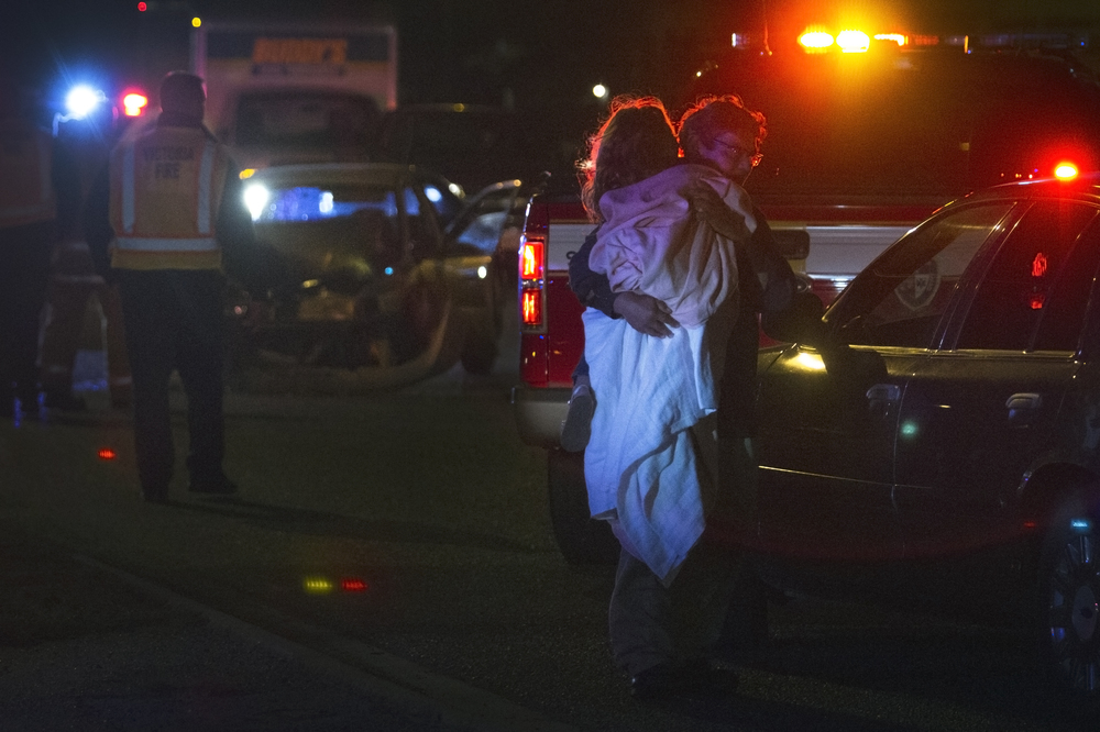 A young girl is comforted at the scene of a collision between a pickup truck and sedan after the truck failed to yield at an intersection on Friday, February 5, 2016, in Victoria, TX. There were five passengers in the sedan, four of which were children. The pickup truck had three passengers. One child and the driver of the sedan were transported to the hospital.