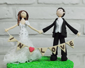 couple with banner wedding cake topper